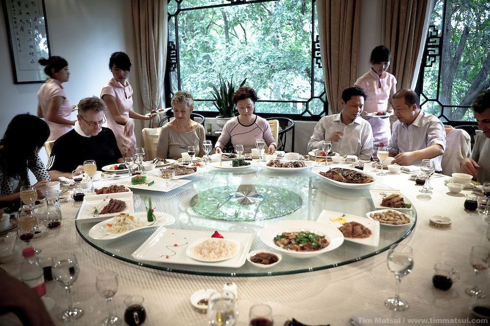 Western photographers and their Chinese hosts with the Yangzhou Press Corporation dine in Yangzhou, China. Yangzhou is a suburb city of Shanghai and major producer of photovoltaic cells for solar power.