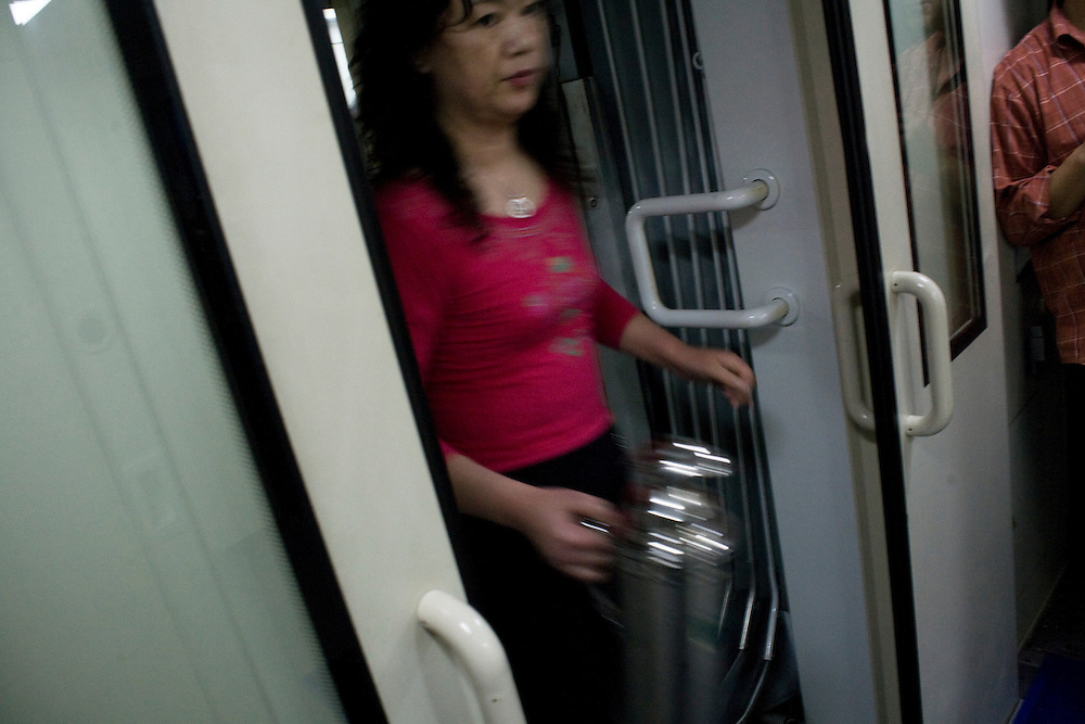 A passenger is going to get hot water in the corridor of the night-train fro Guangzhou to Beijing. Feb 2010.