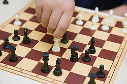 Primary school boy playing a game of chess in an after school club,