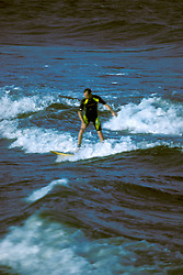 Surfer rides in surf on the beach in Stone Harbor, NJ.