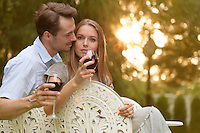Romantic young couple having red wine on chairs in park