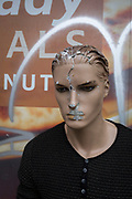 The damaged head and face of an old mannequin in front of graffiti and a Tesco hoarding at Elephant and Castle shopping centre, on 29th March, 2018 in London, England.