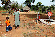 A woman and her son stand in front of their temporary home, which is surrounded by mine-fields, near Mallavi in northern Sri Lanka
