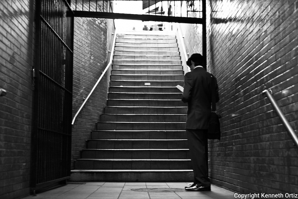 A young man reads his book before he leaves the subway station. New York City.