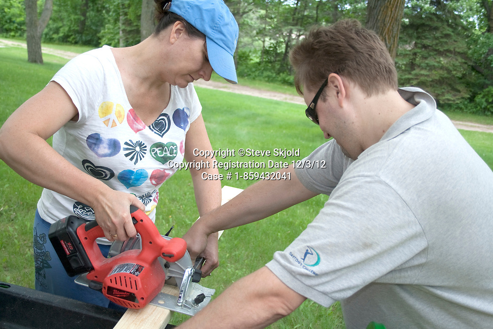 Husband and wife team age 41 and 39 constructing tree house for their kids. Clitherall Minnesota MN USA