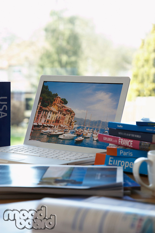 Travel guides next to laptop on table