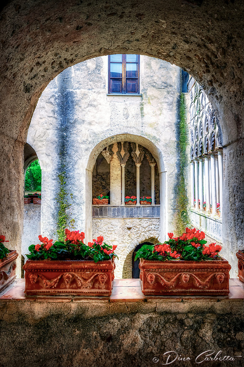 """""""Moorish style cloister and gardens in Villa Rufolo, Ravello""""…<br /> <br /> The Villa Rufolo, which overlooks the Piazza Vescovado, is the historical and cultural center of Ravello. Built by a wealthy merchant family in the 13th century, the villa has a rich and storied past. Boccaccio, one of the earliest authors of the Italian renaissance, wrote a story about the villa and its owner in his Decameron. In its prime, it was one of the largest and most expensive villas on the Amalfi Coast, and legends grew about hidden treasure on its premises. When Sir Francis Neville Reid, a Scottish botanist, visited the villa in 1851, age and neglect had taken a toll on the villa and many of the rooms had fallen into ruin. Reid, however, fell in love with the Moorish towers and the expansive views. He purchased the villa and began an extensive renovation of the gardens and the remaining rooms. The town has become known as """"la città della musica"""", city of music, and for the past several decades the Villa Rufolo has been the center of an annual summer concert series that features piano concerts, chamber music, and a grand orchestral performance on a stage built jutting out over the Mediterranean Sea and the rugged Amalfi Coast below. The gardens and grounds of the Villa Rufolo are open year-round and attract visitors from all over the world. Juxtaposed against the sea, the sky, umbrella pines, and the Church of the Annunziata below, the gardens, with their profusion of flowers, have a magical quality to them. The villa itself contains two large towers and the larger of them stands next to a magnificent Moorish style cloister. Because of the magnificent gardens, the Moorish architecture, and the inspiring vistas, the Villa Rufolo is often described as a smaller version of Spain's famed Alhambra. Traversing the Amalfi Coast was as thrilling as it sounds. The small towns built into the cliffside along the Mediterranean Sea romanticize of glorious past and envisage adventures to come."""
