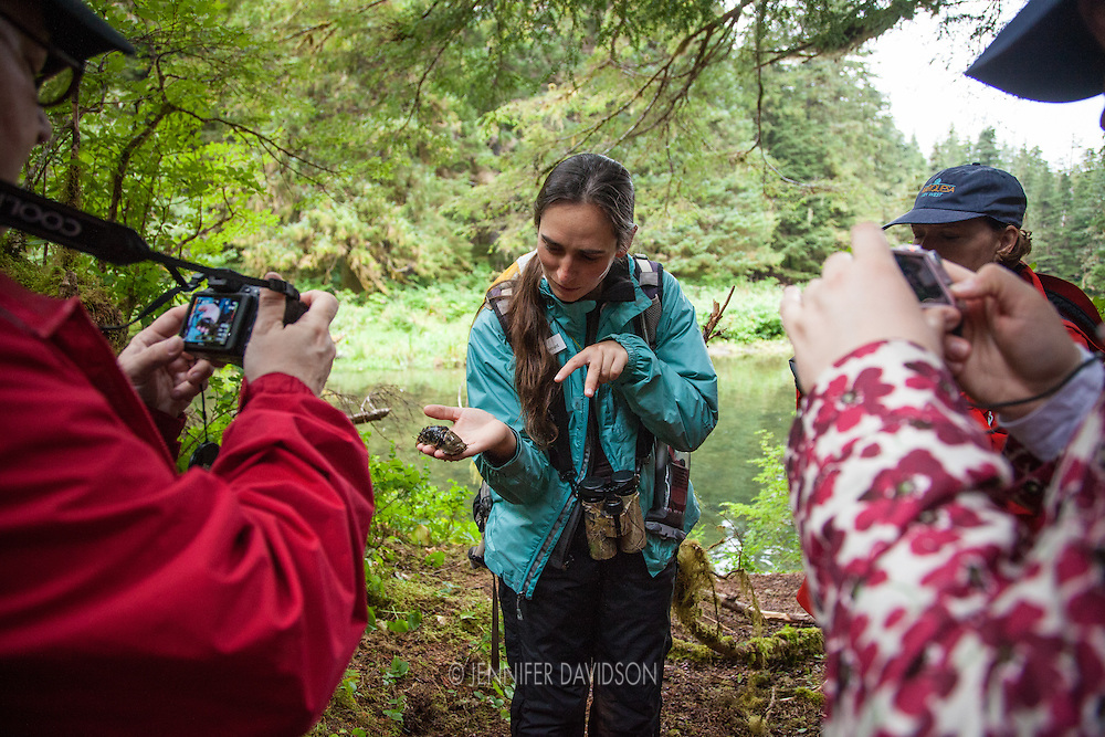 Lindblad-National Geographic Expeditions' Naturalist Emily Mount shows guests from the National Geographic Sea Lion a banana slug during a hiking excursion along Lake Eva Trail, Southeast Alaska.