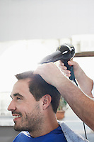 Barber drying mans hair in barber shop