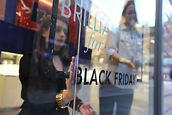 © Licensed to London News Pictures. 24/11/2017. Leeds, UK. Picture shows two shop assistants fixing a Black Friday sticker to a shop window in Leeds this morning. Photo credit: Andrew McCaren/LNP