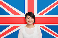 Portrait of young Asian woman smiling against British flag
