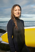Female surfer holding surfboard on beach portrait