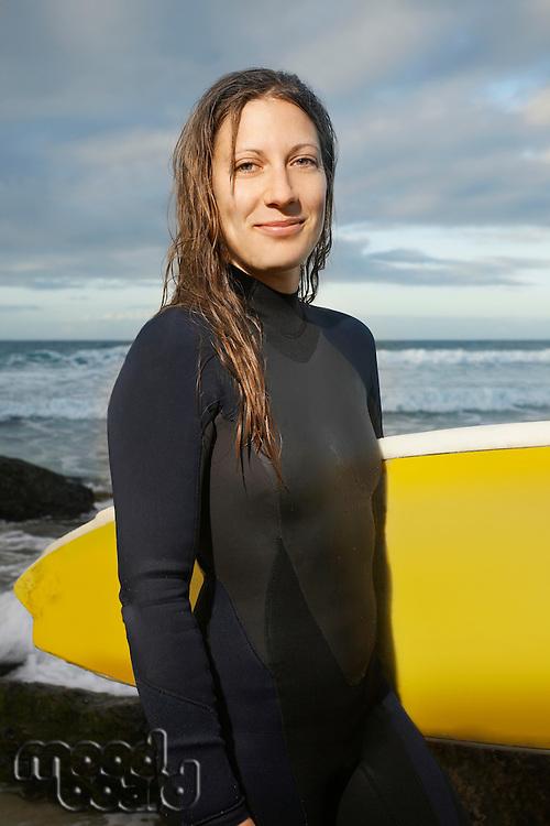 Female surfer holding surfboard on beach portrait