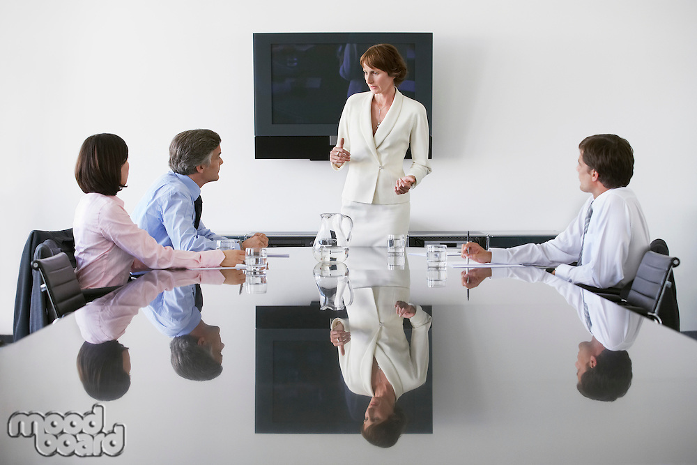 Business woman talking to colleagues in conference meeting