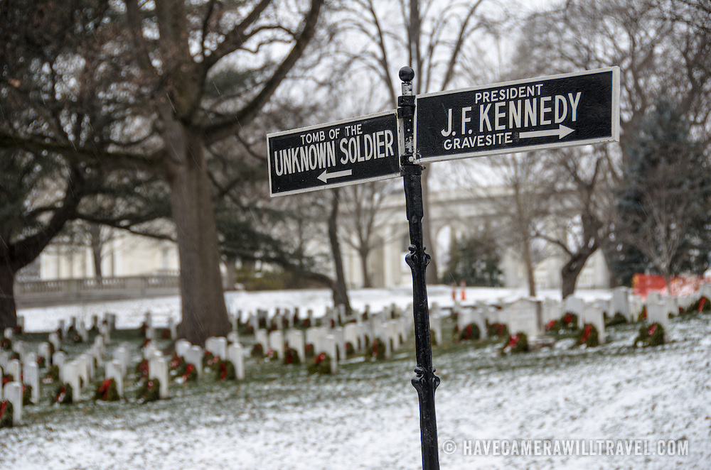 A sign points the ways to the Tomb of the Unkowns and John F. Kennedy's gravesite at Arlington National Cemetery in the snow. Arlington, Virginia, United States.