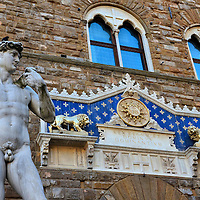 """David Statue in Front of Palazzo Vecchio in Florence, Italy<br /> In the late 15th century, two artists failed to convert a huge block of Carrara marble called """"The Giant"""" into a statue of David that was supposed to sit atop the Basilica di Santa Maria del Fiore (Duomo). Then Michelangelo, at the age of 26, was given the chance.  After more than two years of work, the 17 foot masterpiece was unveiled in Piazza della Signoria.  In 1910, it was replaced by this replica. You can see the original in the Accademia Gallery in Florence.  In the photo's background is the Monogram of Christ over the entrance of Palazzo Vecchio."""