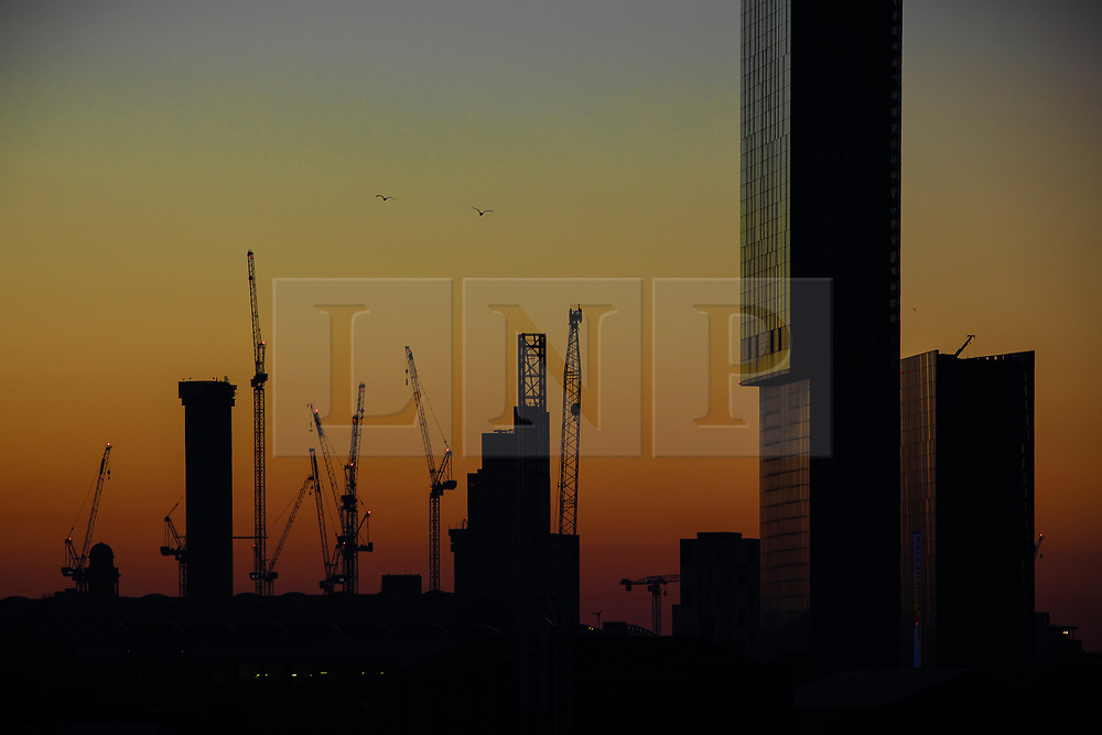 © Licensed to London News Pictures . 26/02/2019. Manchester , UK . Dawn rises over the Manchester skyline as today (Tuesday 26th February 2019) promises to be another unseasonably warm day following yesterday's record-breaking warmth . Photo credit: Joel Goodman/LNP