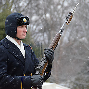 A soldier takes part in the changing of the guard ceremony at the Tomb of the Unknowns at Arlington National Cemetery in the snow.