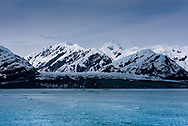 A glacier and snow-capped mountains  loom before blue Alaskan waters carrying chunks of glacier ice.