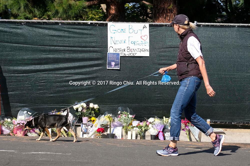 7月21日,在美国洛杉矶帕洛斯弗迪斯庄园,一名女人拉著她的狗经过林肯公园&rdquo;乐队主唱切斯特&middot;本宁顿屋外。美国警方20日证实,著名摇滚乐队&ldquo;林肯公园&rdquo;的主唱切斯特&middot;本宁顿当天在洛杉矶家中疑似自杀身亡,终年41岁。新华社发 (赵汉荣摄)<br /> A woman walks her dog past a memorial site outside of Chester Bennington's home of  in Palos Verdes Estates, California, the United States, on Friday, July 21, 2017. Chester Bennington, lead singer of alt-rock band Linkin Park, was found dead on Thursday morning in his Palos Verdes Estates home of an apparent suicide. He was 41.(Xinhua/Zhao Hanrong)(Photo by Ringo Chiu)<br /> <br /> Usage Notes: This content is intended for editorial use only. For other uses, additional clearances may be required.