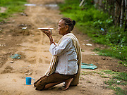 "20 JUNE 2016 - DON KHONE, CHAMPASAK, LAOS: A woman prays while she waits for monks from Wat Khone Nua on their morning alms' rounds, called the ""tak bat"" in Don Khone village on Don Khone Island. Don Khone Island, one of the larger islands in the 4,000 Islands chain on the Mekong River in southern Laos. The island has become a backpacker hot spot, there are lots of guest houses and small restaurants on the north end of the island.     PHOTO BY JACK KURTZ"