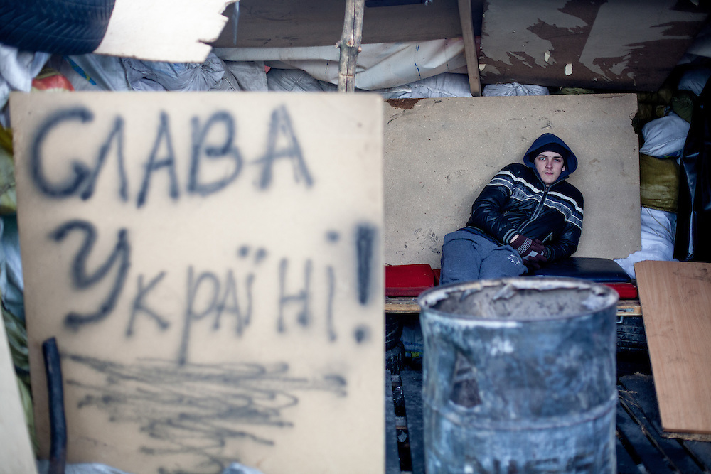 "Young protestor Roman at the barricades blocking a building supplies store named ""Epicenter"" in the city of Lviv, Ukraine. The inscription reads ""Glory for the Ukraine"" (Slavo Ukraina)."