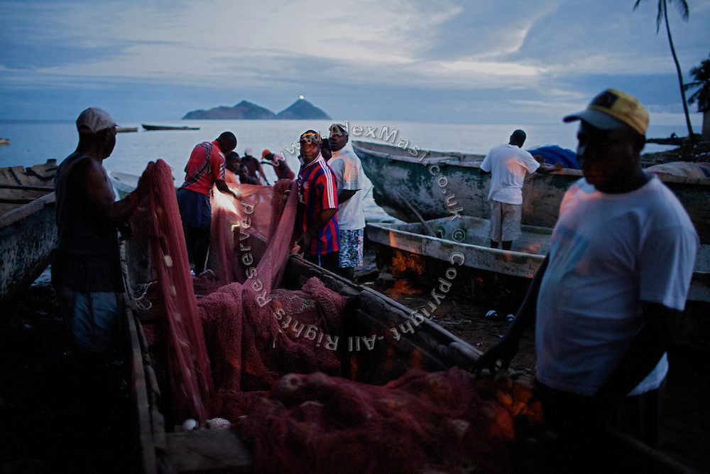 At sunrise, fishermen are preparing their nets before venturing into the sea with their boat in Praia Cruz, on the island of Sao Tome, Sao Tome and Principe, (STP) a former Portuguese colony in the Gulf of Guinea, West Africa.