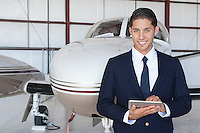 Portrait of handsome young pilot using tablet PC in front of airplane