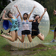 Participants pose for a photographer after riding in a Zorb Globe. The sport of Zorb globe riding was invented in New Zealand and globes are designed, manufactured and tested there, The Zorb globe is an 11 foot high inflatable transparent sphere which you can ride inside. Two feet of air protect participants from the ground enabling you to globe ride down hills at high speed.  Agrodome, Western Road. Ngongotahaha.  Rotorua, New Zealand,, 11th December 2010 Photo Tim Clayton.