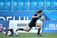 Kurt Baker of New Zealand evades the tackle of Daniel Norton of England during the semi final of the medal competition of the Rugby Sevens between New Zealand and England held at Delhi University as part of the XIX Commonwealth Games in New Delhi, India on the 12 October 2010..Photo by:  Ron Gaunt/photosport.co.nz