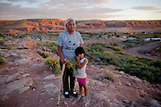 Daisy Yazzie, 66, of Tuba City takes a walk to pick flowers with her granddaughter Abigail Yellow, 4, outside of their home in the Navajo Nation. Many Navajo elders fear that the younger generation will not speak the language as the number of fluent Navajo speakers dwindles. (For The New York Times)