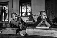 Two young nun apprentices enjoy a brief moment of whimsy during a prayer lesson in a nunnery. Bhumtang, Bhutan.
