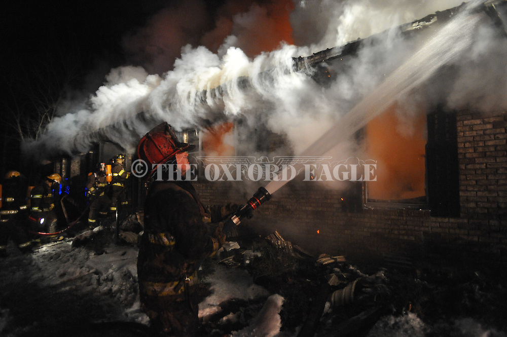 Lafayette County fireman Matt Hinkle fights a fire at the home of Freddie Pinion at 852 Highway 30 east of Oxford, Miss., on Thursday, January 13, 2011. Everyone escaped the house safely.