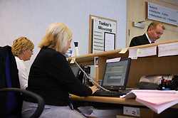 Work colleagues working on reception at the NHS offices,