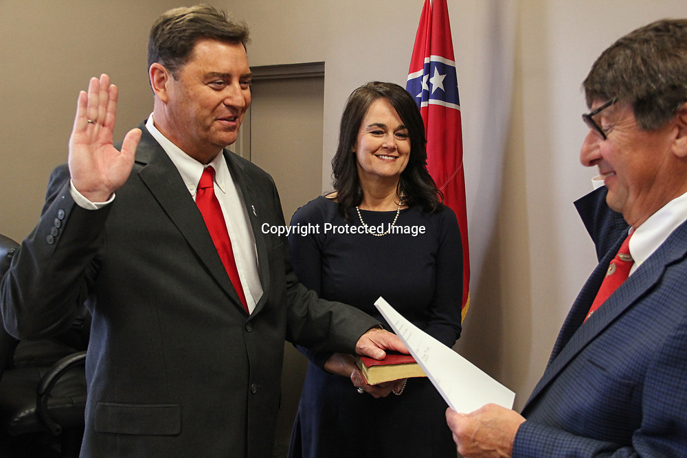 ADAM ARMOUR I BUY AT PHOTOS.ITAWAMBATIMES.COM<br /> FULTON OFFICIALS SWORN IN- Barry Childers, his wife Sarah by his side, takes the oath of office as mayor of Fulton before Judge Mike Mills during a special ceremony Monday afternoon. Although Fulton&rsquo;s new board, including returning members Liz Beasley, Hayward Wilson, Joey Steele and Mike Nanney and newcomer Brad Chatham, along with newly-appointed police chief Mitch Nabors, were sworn in this week, they won&rsquo;t actually take office until July 3.