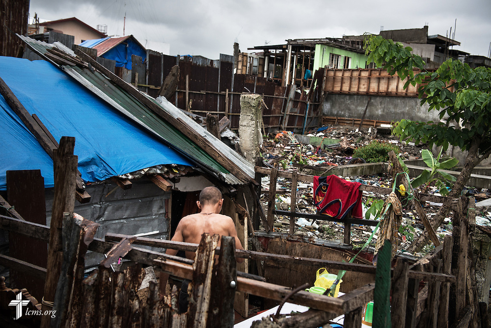 A man works in his home set against a backdrop of destruction left behind from Typhoon Haiyan in Tacloban, Leyte Province, Philippines, on Friday, March 14, 2014. LCMS Communications/Erik M. Lunsford