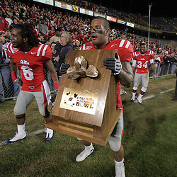 22 November 2008: Jeremy McGee (6) walks alongside teammate Mississippi linebacker Tony Fein (47) as he carries the Magnolia Trophy given to the winner of the rivalry game between Ole Miss and LSU, the Ole Miss Rebels defeated the LSU Tigers 31-13 victory at Tiger Stadium in Baton Rouge, LA.