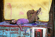 Varanasi, India. Exhausted, this young Indian Man is resting on a street stall after a full day of crazy celebration for the Holy Festival.<br />