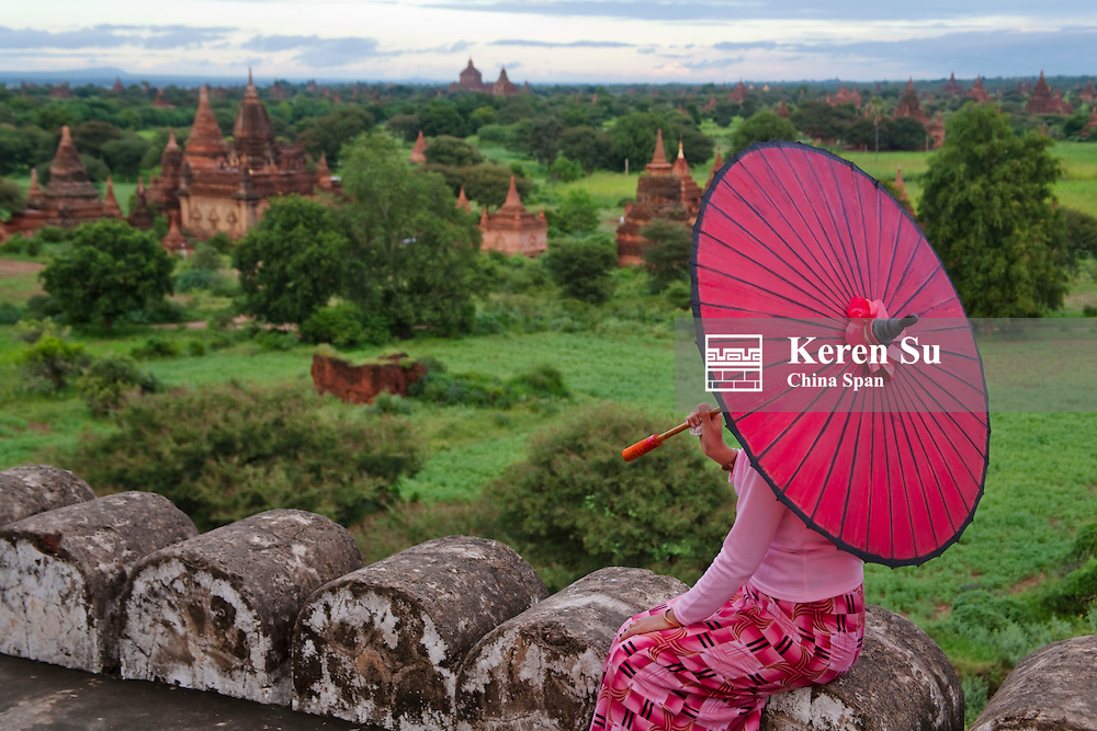 Girl with red umbrella overlooking temples of  Bagan, Myanmar