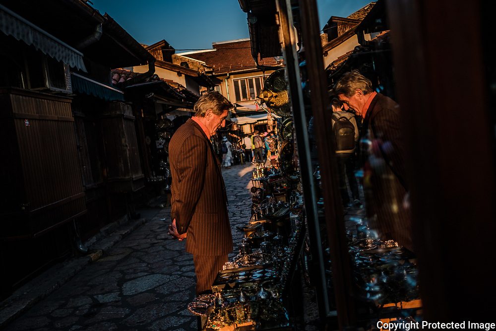 A man looks at items for sale at  shop in Sarajevo's Old Town. Some of the local metal workers are turning the discarded bullet casings and shells from the war into items that can be sold to tourists. A part of a growing war tourism industry in Sarajevo.
