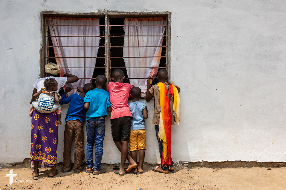 Patients peek into the window of the clinic on the third day of the LCMS Mercy Medical Team on Wednesday, May 9, 2018, in the Yardu village outside Koidu, Sierra Leone, West Africa. LCMS Communications/Erik M. Lunsford