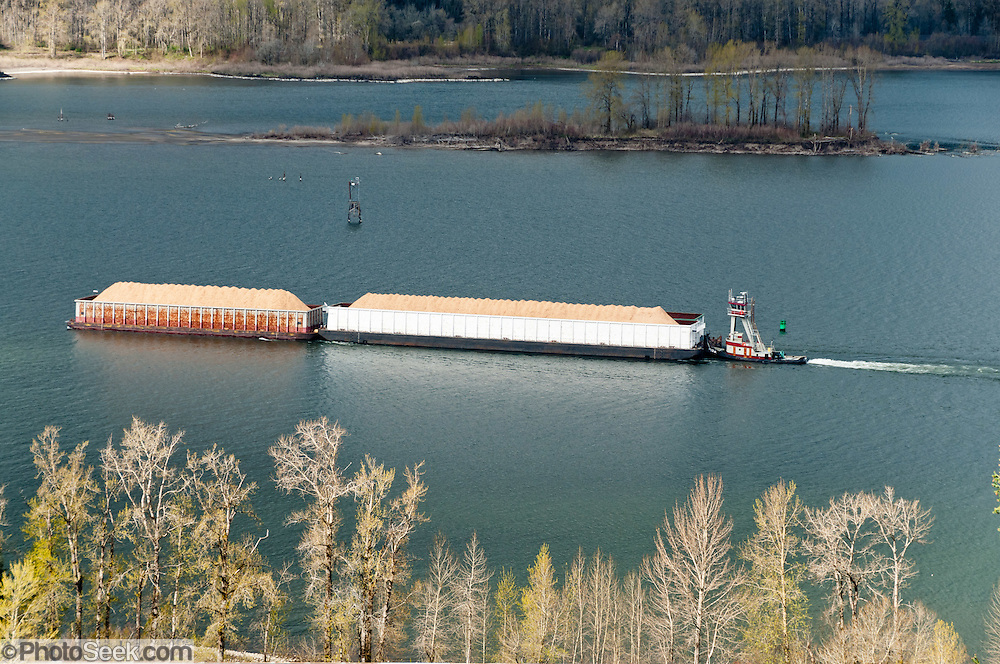 A tugboat pushes barges of grain, in Columbia River Gorge National Scenic Area, Oregon, USA.