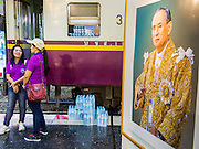 "05 DECEMBER 2013 - BANGKOK, THAILAND:  With a portrait of Bhumibol Adulyadej, the King of Thailand, in the foreground, women wait to board a special train on the 86th birthday of Bhumibol Adulyadej, the King of Thailand. Dec. 5, the King's Birthday, is a national holiday in Thailand, and is also celebrated as the country's ""Fathers' Day."" The State Railways of Thailand put on special trains to take people to the King's ""Summer Palace"" in the oceanside community of Hua Hin where the King granted a public audience. There were also merit making ceremonies throughout the country. Many people wear yellow on the King's Birthday because yellow is the color associated with his reign. As of 2013, he was the longest reigning monarch in the world.     PHOTO BY JACK KURTZ"