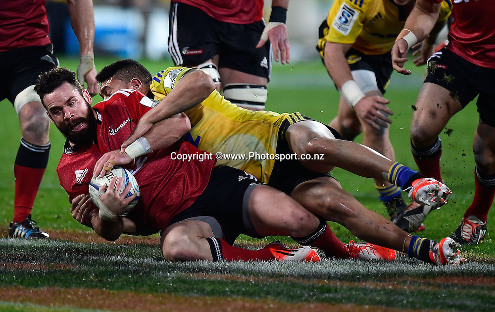 Ryan Crotty captain of the Crusaders is tackled by Ardie Savea of the Hurricanes during the Super Rugby - Hurricanes v  Crusaders rugby match at the Westpac Stadium in Wellington, New Zealand on the 28th of June 2014. Photo: Marty Melville/www.Photosport.co.nz