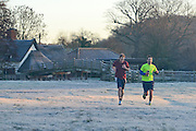 © Licensed to London News Pictures. 29/12/2013. East Bergholt, UK. Two men jog across a frosty field. Early morning frost and mist on the River Stour at Deadham Vale this morning 29th December 2013. Photo credit : Stephen Simpson/LNP