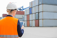 Rear view of female engineer using digital tablet in shipping yard
