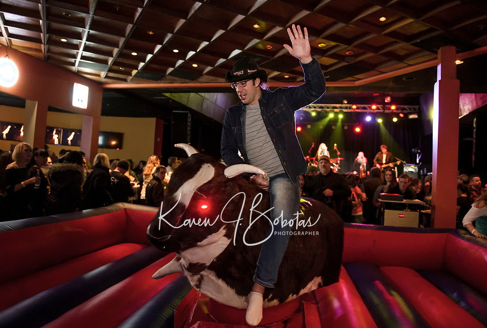 Stephen Colby goes a couple of rounds with the Mechanical Bull with the Jodie Cunningham Band on stage Saturday night for opening weekend at the Whiskey Barrel in downtown Laconia.  (Karen Bobotas/for the Laconia Daily Sun)