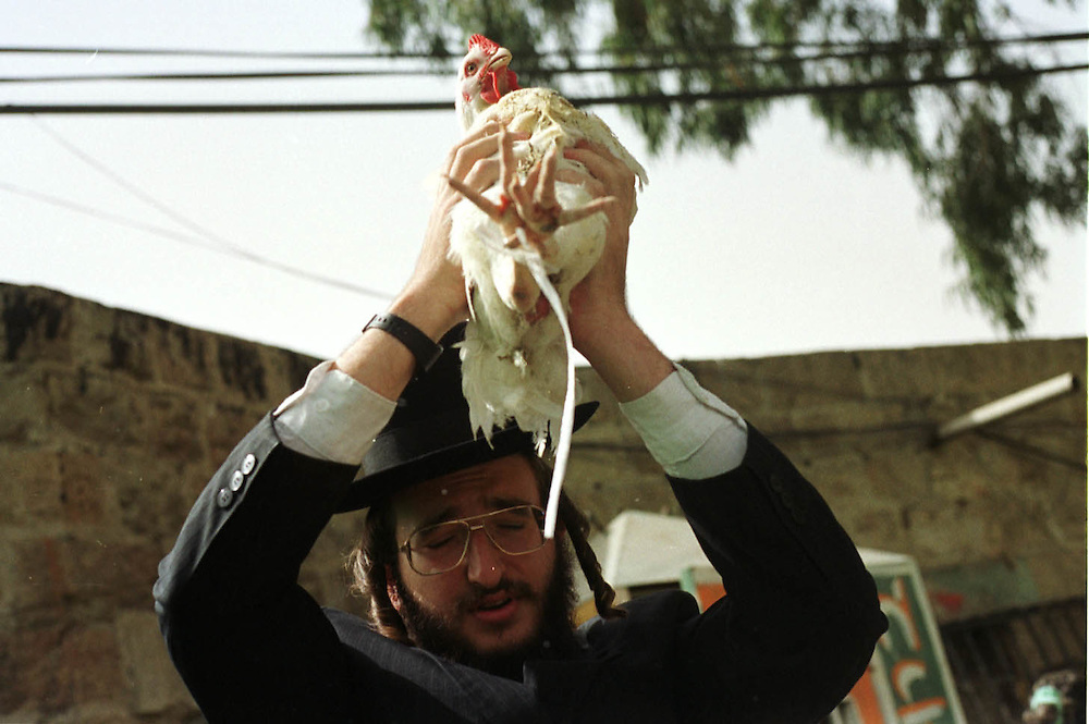 An ultra-Orthodox Jew swings a chicken over a woman head during Kaparot in Jerusalem September 18, 2004. Kaparot is an ancient custom connected to the Jewish Day of Atonement, Yom Kippur, where white chickens are slaughtered as a symbolic gesture of atonement. The slaughtered chickens are then donated to the poor.