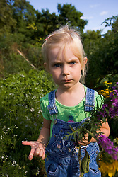 A young girl in a garden in Gloucester Massachusetts USA