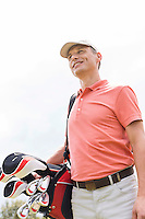 Happy middle-aged man looking away while carrying golf bag against clear sky
